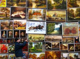 Vendedor pendura quadros em um dos muros da stare miasto, o centro histórico de Cracóvia