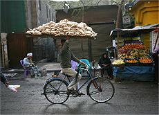 Jovem pedala pelo Cairo com tabuleiro de pão na cabeça