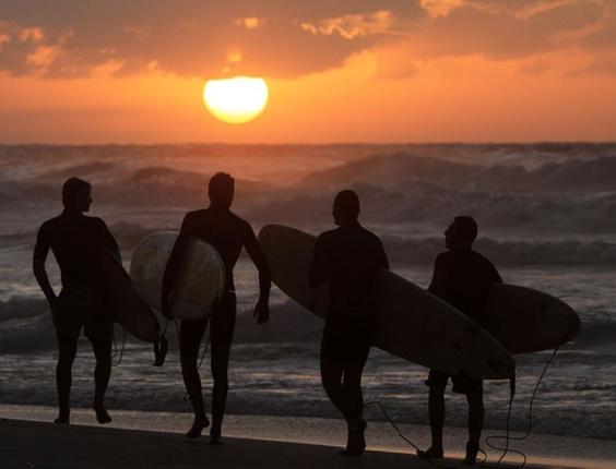 Jovens palestinos carregam suas pranchas de surfe, durante pôr do sol em Gaza