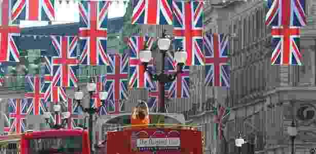Turista fotografa bandeiras britânicas penduradas no centro de Londres do alto do ônibus turístico da cidade - Toby Melville/Reuters - Toby Melville/Reuters