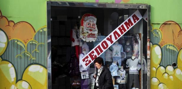 """Loja com cartaz de """"vende-se"""" no centro de Atenas, na Grécia (22.12.2011)"""